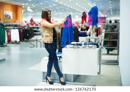 Attractive woman choosing cloths in shop - stock photo