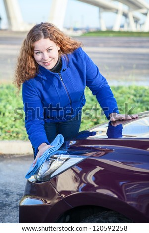 Attractive woman cleaning car headlights - stock photo