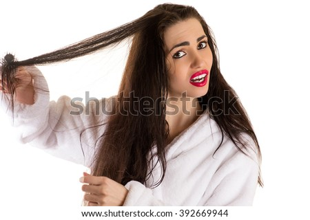 attractive woman combing hair with sad face - stock photo