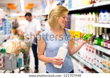 Attractive woman customer choosing shampoo in cosmetics department