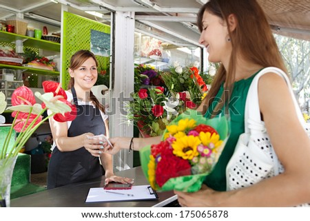 Attractive woman customer client playing with cash money for a small bouquet of sunflowers in a florist shop, with the business owner smiling happily and holding a bill.  Working business outdoors. - stock photo