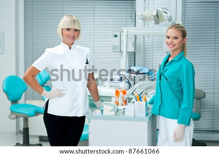 attractive woman dentist standing in her office with her assistant - stock photo