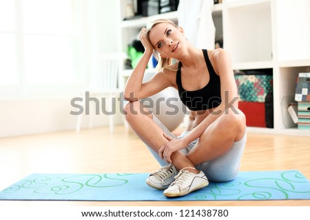 Attractive woman do fitness exercise at home on a blue mat - stock photo
