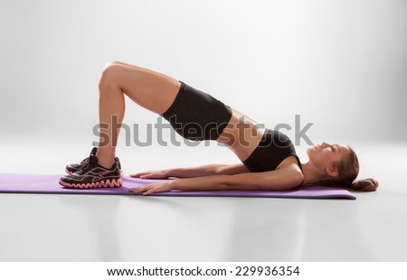 Attractive woman do fitness exercise on a lilac mat on grey background - stock photo