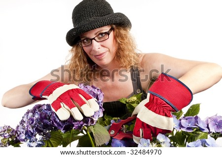Attractive woman does gardening with secateurs on white background - stock photo