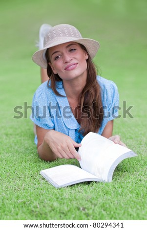 attractive woman dreaming on grass with book - stock photo