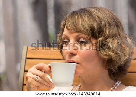 Attractive woman drinking a cup of coffee on wooden chair.