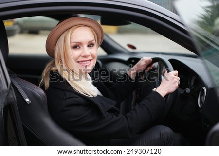 Attractive woman driver in a stylish hat sitting behind the steering wheel in her car looking through the open door at the camera with a friendly smile - stock photo