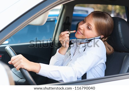 attractive woman driving the car, painting her lips and talking on mobile phone