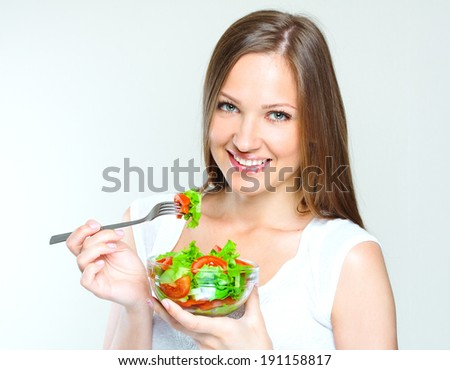 attractive woman eating salad with vegetables. healthy food.