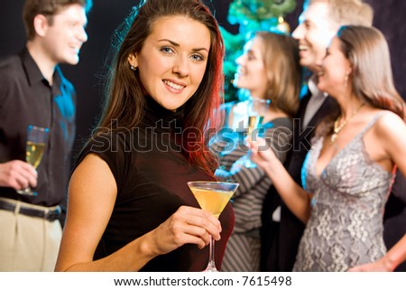 Attractive woman enjoying a cocktail while a party
