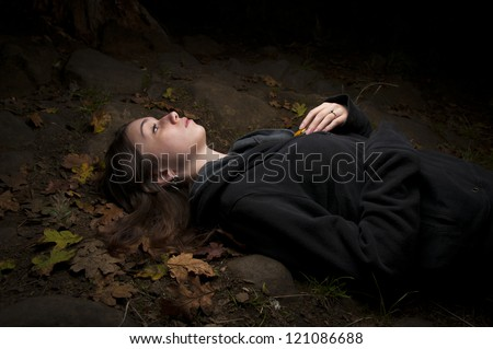 Attractive woman enjoying nature lying on her back in darkness lost in thought thinking deeply amongst fallen autumn leaves with copyspace - stock photo