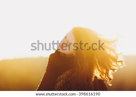 Attractive woman enjoying sunlight with hair flying in wind. She is carefree, happy and calm. The sunny winter day and the air filled by warm sunlight. - stock photo