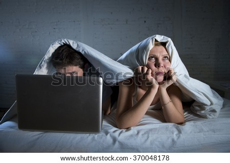 attractive woman feeling upset unsatisfied and frustrated in bed at night with his husband while man work on computer laptop ignoring her in married couple problem and relationship communication issue - stock photo