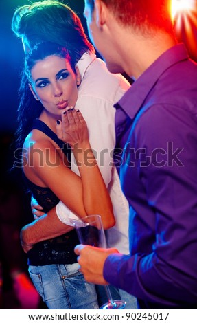 Attractive woman flirting with man in nightclub, while dancing with another.? - stock photo