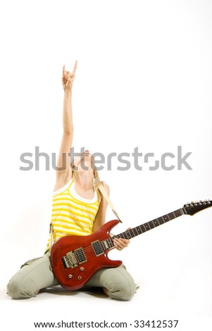 attractive woman guitarist making a rock sign seated on the ground