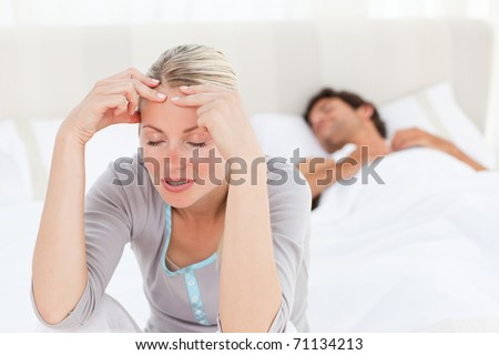 Attractive woman having a headache while her husband is sleeping at home - stock photo