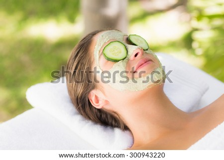 Attractive woman having cucumber on her face at spa center - stock photo