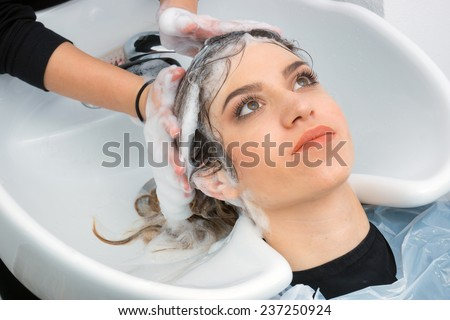attractive woman having hair washed in salon - stock photo