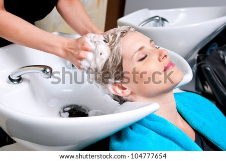 attractive woman having her hair washed in salon - stock photo