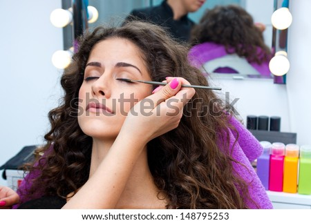 attractive woman having mascara make up applying in salon