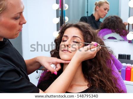 attractive woman having mascara make up applying in salon - stock photo