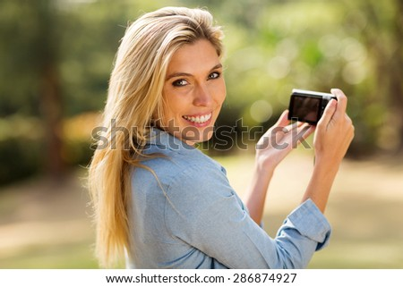 attractive woman holding a camera outdoors