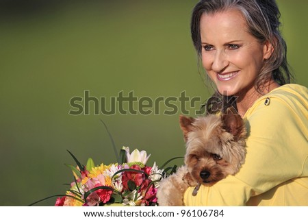 Attractive woman holding adorable Yorkshire Terrier - stock photo