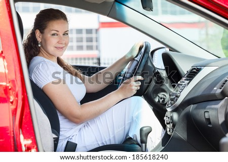 Attractive woman holding car wheel through the opened door - stock photo
