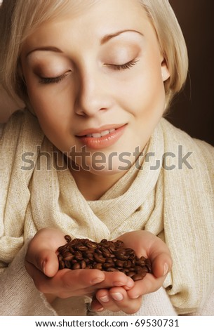 Attractive woman holding coffee beans. - stock photo
