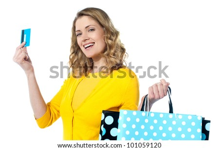 Attractive woman holding credit card with shopping bags smiling against white background - stock photo