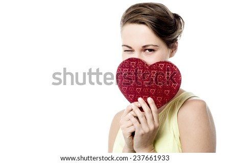 Attractive woman holding heart shape gift box