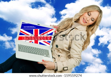 attractive woman holding laptop with english language learning sign on the screen