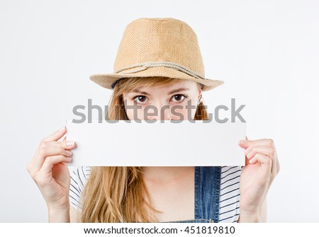 Attractive woman holding paper blank in her hands. Portrait of emotional young woman showing surprised and happy emotions. Girl in summer hat - stock photo