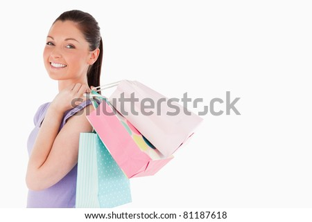 Attractive woman holding shopping bags while standing against a white background - stock photo