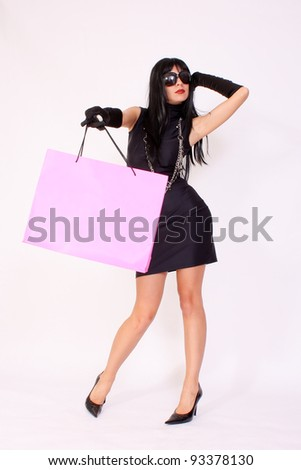 Attractive woman holding shopping paper bag - stock photo