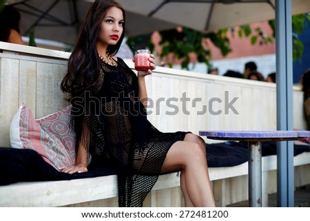 Attractive woman in a bikini drinking a fruit cocktail while relaxing in sidewalk beach cafe,  beautiful young woman enjoying a fruit smoothie during her summer holidays en Barcelona - stock photo