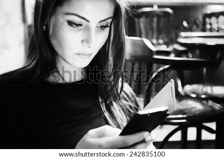 Attractive woman in a cafe reading a text message from her phone  - stock photo