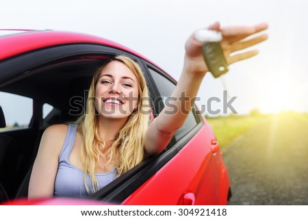 Attractive woman in a car showing keys at sunset. - stock photo