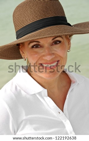 Attractive Woman in a White Top Wearing a Brown Summer Hat - stock photo