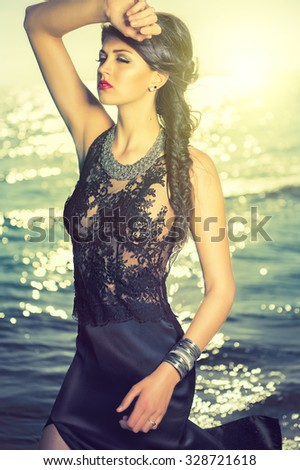 attractive woman in an elegant dress on the beach - stock photo