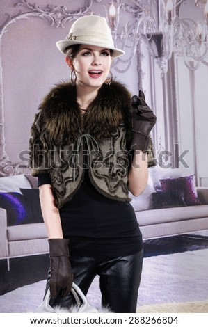 attractive woman in autumn/winter clothes holding handbag posing