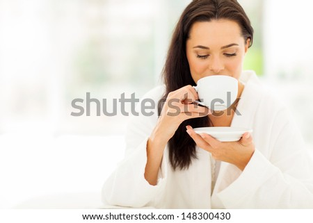 attractive woman in bathrobe drinking coffee in bedroom - stock photo