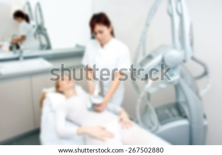 attractive woman in beauty salon on cellulite treatment therapy, blurred for presentation, abstract background - stock photo