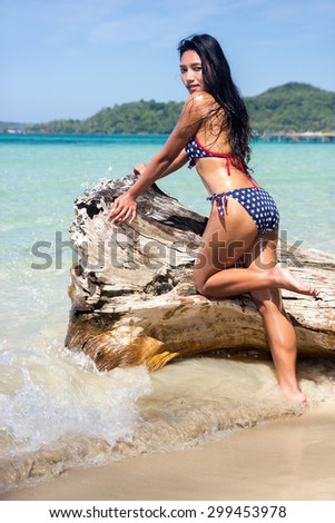 attractive woman in bikini on the withered trunk over the sea - stock photo