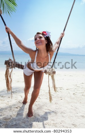 attractive woman in bikini  playing with swing on a sea background - stock photo