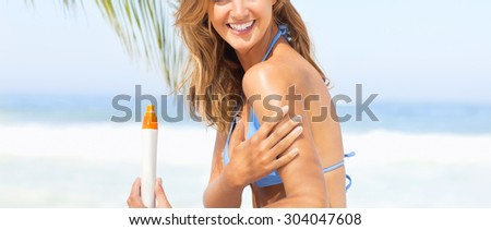 Attractive Woman In Bikini Sitting At Beach With Sun Protection Cream - stock photo