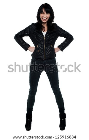 Attractive woman in black attire standing with hands on her waist. - stock photo