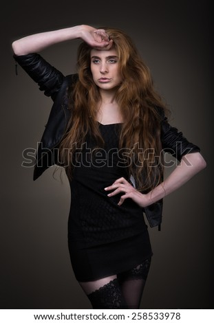 Attractive woman in black dress, leather jacket and stockings.