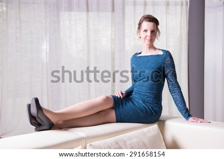 attractive woman in blue dress sitting on couch - stock photo